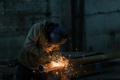 Worker welding metal with sparks at factory. Royalty Free Stock Photography