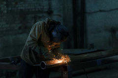 Worker welding metal with sparks at factory. Worker welding metal with sparks at factory Royalty Free Stock Photos