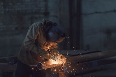 Worker welding metal with sparks at factory. Stock Photos