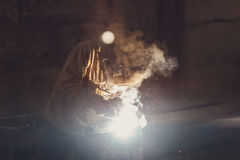 Worker welding metal with sparks at factory. Worker welding metal with sparks at factory, toned Stock Photos