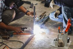 Worker without welding protective gloves welding metal. Royalty Free Stock Images