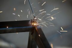 Worker is welding sparks table steel. Royalty Free Stock Image
