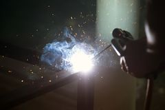 Worker is welding sparks table steel. Stock Image