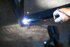 Worker is welding sparks table steel. Royalty Free Stock Images