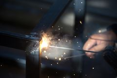 Worker is welding sparks table steel. Stock Images