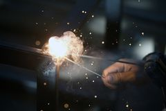 Worker is welding sparks table steel. Stock Photo