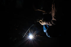 Worker welding steel. In dark room Royalty Free Stock Photography
