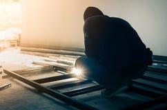 Worker welding steel in dark room Stock Photos
