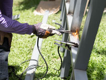 Worker welding a Steel Iron Bar for a New Fence Frame Stock Photo