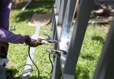 Worker welding a Steel Iron Bar for a New Fence Frame Royalty Free Stock Photography