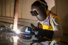 Worker welding the steel part. Worker welding the steel part in factory Stock Photo