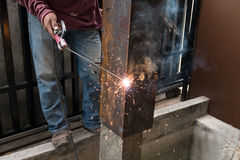 Worker welding steel with spark lighting and smoke at constructi Stock Image