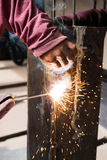 Worker welding steel with spark lighting and smoke at constructi. On site Royalty Free Stock Photography