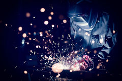 Worker welding steel with sparks using mig mag welder. Focus on sparks Stock Photos