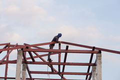 Worker welding the steel to build the roof. At construction site Stock Photo