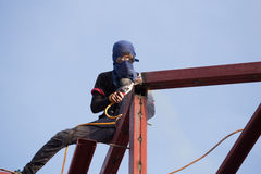 Worker welding the steel to build the roof. At construction site Royalty Free Stock Photo