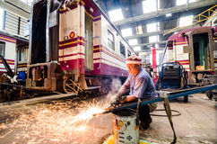 Worker welding train in the factory. Stock Image
