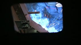 Worker welds an iron. Worker in protection mask are welding iron at plant