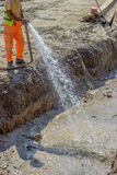 Worker wets the crushed aggregate base course surface. Before compaction during pipeline construction Stock Image