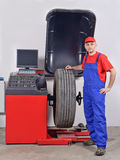 Worker at wheel balancing machine Stock Images