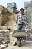 Worker with wheelbarrow Stock Images