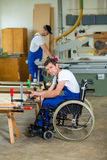 Worker in wheelchair in a carpenter's workshop Royalty Free Stock Photos