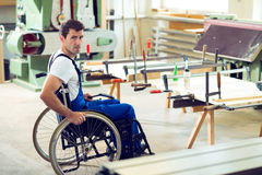 Worker in wheelchair in a carpenter's workshop. Disabled worker in wheelchair in a carpenter's workshop Royalty Free Stock Image