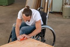 Worker in wheelchair in a carpenter`s workshop. Disabled worker in wheelchair in a carpenter`s workshop royalty free stock photography