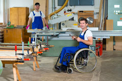 Worker in wheelchair in a carpenter's workshop with his colleagu Royalty Free Stock Photo