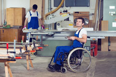 Worker in wheelchair in a carpenter's workshop with his colleagu Stock Images