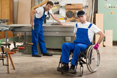 Worker in wheelchair in a carpenter's workshop with his colleagu Royalty Free Stock Images
