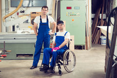 Worker in wheelchair in a carpenter's workshop with his colleagu Stock Photos
