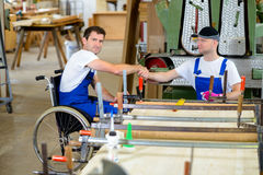 Worker in wheelchair in a carpenter's workshop with his colleagu Stock Photo