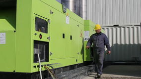 Worker who operates two powerful diesel generators that supply an asphalt mixing plant stock video