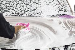 Worker wipe clean car using detergent soap foam with cloth. In garage royalty free stock images