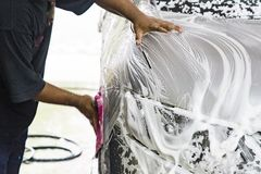 Worker wipe clean car using detergent soap foam with cloth. In garage stock images