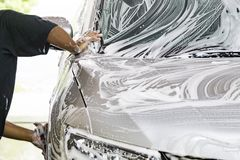 Worker wipe clean car using detergent soap foam with cloth. In garage royalty free stock image