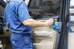 Worker wiping a car door with cloth. Close up of a male worker wearing uniform and wiping a car door with a microfiber cloth in the garage Stock Photos