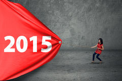 Worker woman draw number 2015. Casual woman try to drag number 2015 on a big banner Stock Image