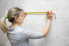Worker woman measuring on wall Royalty Free Stock Image