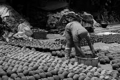 A worker woman on old and traditional Pottery place. Pottery is one of the oldest human inventions, originating before the Neolithic period, with ceramic objects Royalty Free Stock Photo