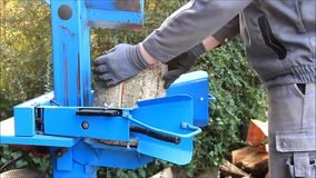 Worker with wood splitter in action, hydraulic, electric, firewood stock video footage