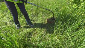 Worker in overalls mowing the tall grass trimmer. Worker in work clothes mowing the tall grass trimmer stock video footage