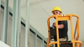 Worker at work in the construction of a plasterboard wall stock video footage