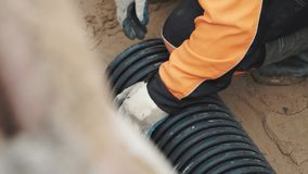 Worker in work gloves rubber boots placing plastic pipe on sand to measure it stock video