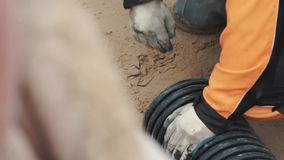 Worker in work gloves rubber boots pull sand out black plastic pipe stock video