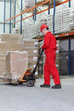 Worker  at work with hand powered pallet jack. Worker in red uniform at work with hand powered pallet jack in warehouse Stock Image
