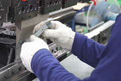 Worker at work on the press brake. Royalty Free Stock Photos