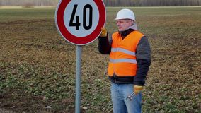 Worker working with adjustable wrench near road sign stock video