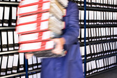 Worker in working clothes, carrying folders. Worker in working clothes, carrying red folders royalty free stock image